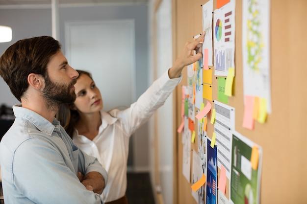 オフィスでグラフを分析する女性の同僚と青年実業家