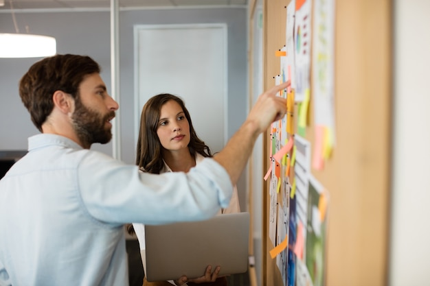 Young businessman with female colleague discussing over charts at office