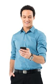 Молодой бизнесмен с рукой в кармане с помощью мобильного телефона