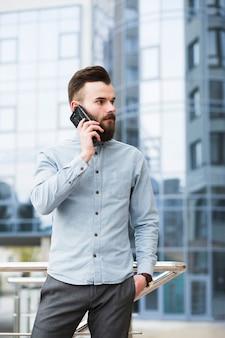 携帯電話で話している彼のポケットに手を持つ青年実業家