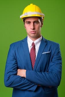 緑の壁にヘルメットを持つ青年実業家
