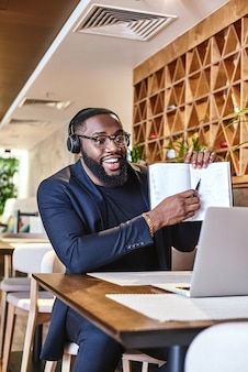 Young businessman with headphones sitting in cafe in front of laptop and networking