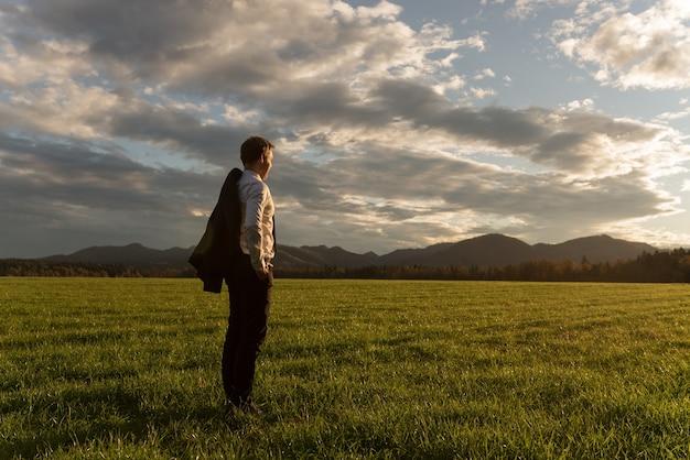 遠くを見つめる劇的な夕方の空の下で美しい緑の牧草地に立って、肩にスーツのジャケットを着た青年実業家。