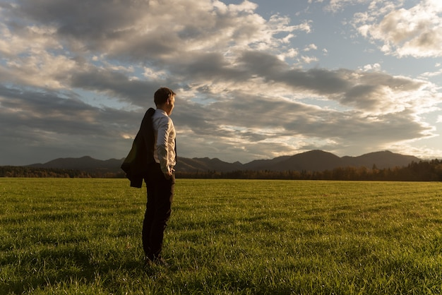 Young businessman with his suit jacket over the shoulder, standing in beautiful green meadow under dramatic evening sky gazing into the distance.