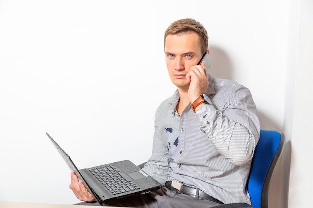 노트북과 전화를 가진 젊은 사업가 그는 긴장하여 화면을 보고 모바일로 말한다