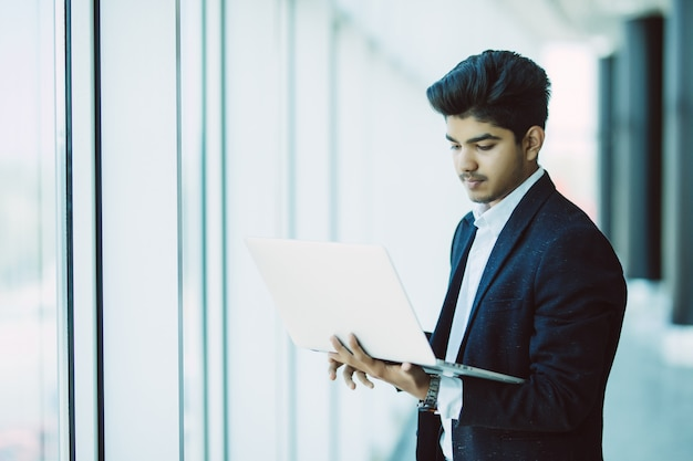 Young businessman with laptop computer working at office