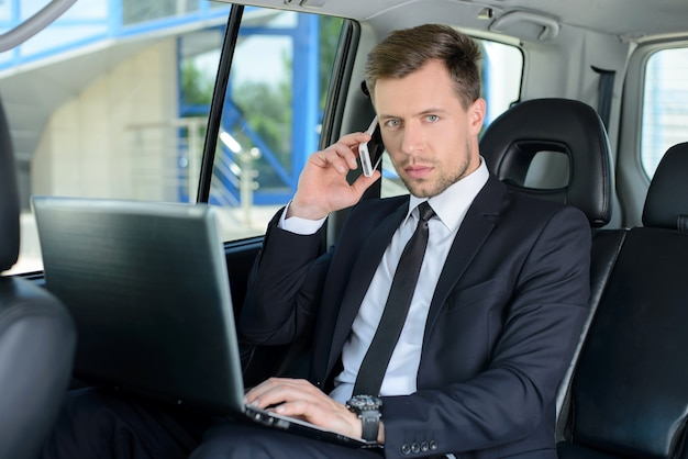 Young businessman with laptop is riding in the car.