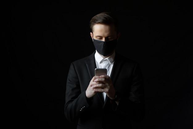 コロナウイルスからの保護のためのマスクを持つ青年実業家