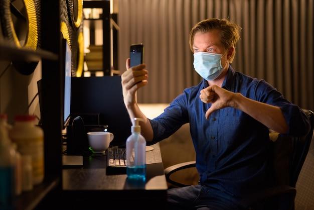 Молодой бизнесмен в маске показывает палец вниз и делает видеозвонок во время работы из дома поздно ночью