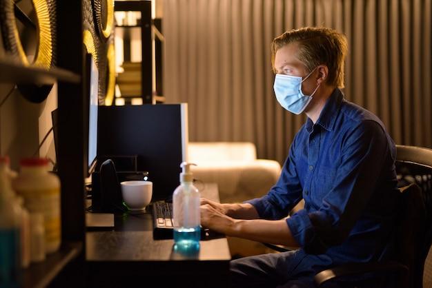 Молодой бизнесмен с маской работает из дома поздно ночью