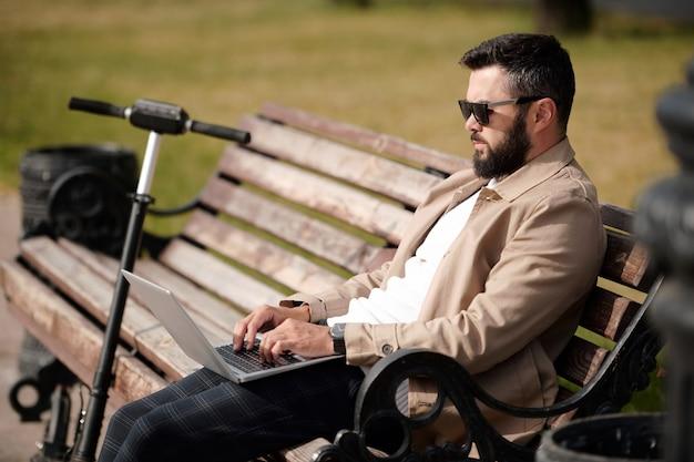 근처에 그의 스쿠터와 함께 따뜻한 날에 공원에서 나무 벤치에 앉아있는 동안 인터넷에서 서핑하는 모바일 가제트와 젊은 사업가