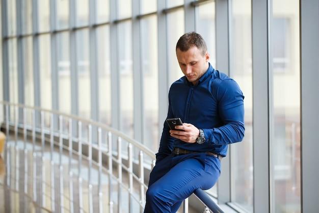 携帯電話を持つ青年実業家。