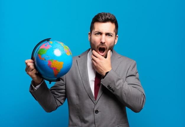 입과 눈을 크게 벌리고 턱에 손을 대고 젊은 사업가, 불쾌하게 충격을 받고 세계 세계지도를 들고 뭐라고 말하거나 와우