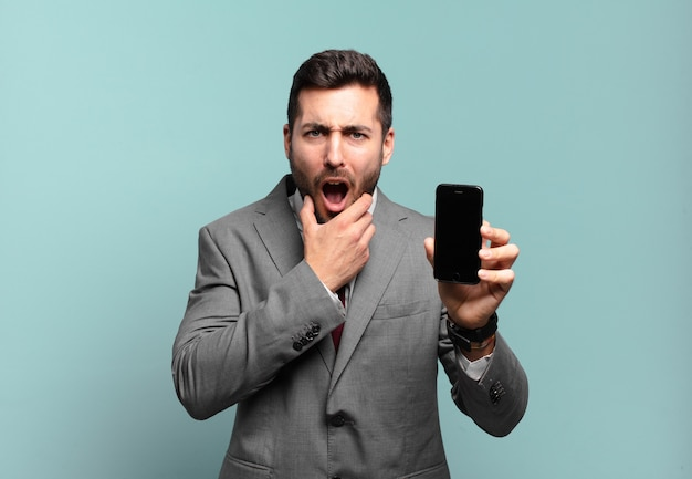 Young businessman with mouth and eyes wide open and hand on chin, feeling unpleasantly shocked, saying what or wow and showing his phone screen