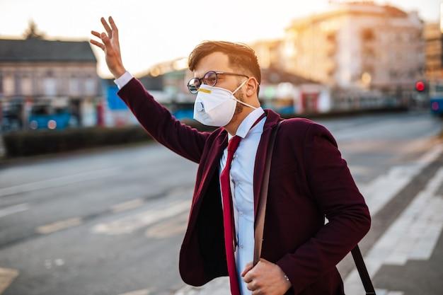 보호 마스크를 쓴 젊은 사업가가 텅 빈 거리에 홀로 서서 버스나 택시를 기다리고 있습니다. 바이러스 전염병 또는 오염 개념.