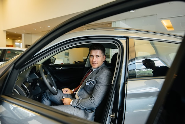 A young businessman with a salesman looks at a new car in a car dealership. buying a car.