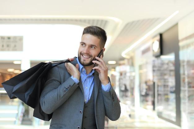 屋内で電話で話している買い物袋を持つ青年実業家。
