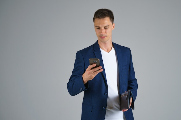 A young businessman with short hair in a blue jacket and white t shirt is holding a phone in his hand and talking against a gray background