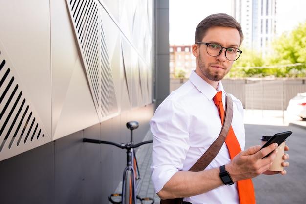 彼の自転車で都市環境に立ってスマートフォンと飲み物を持つ青年実業家
