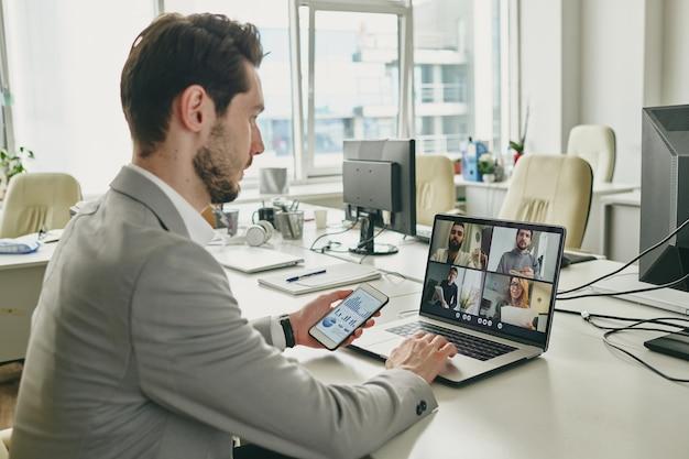 Молодой бизнесмен со смартфоном сидит за столом перед ноутбуком и общается с клиентами онлайн через платформу для конференций