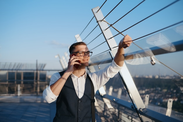 Young businessman with a smartphone standing on the terrace of a business center. close-up.