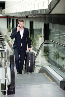 Young businessman with a suitcase and plane tickets.