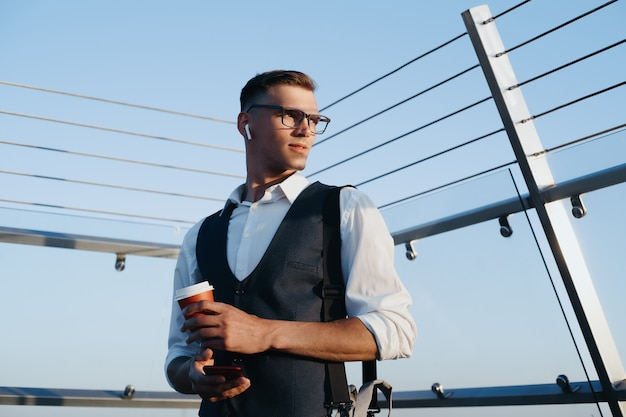 Young businessman with a takeaway coffee standing on the office