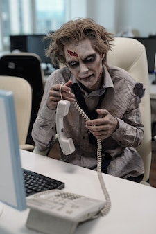 Young businessman with zombie body holding phone receiver while sitting by desk in front of computer monitor in office environment