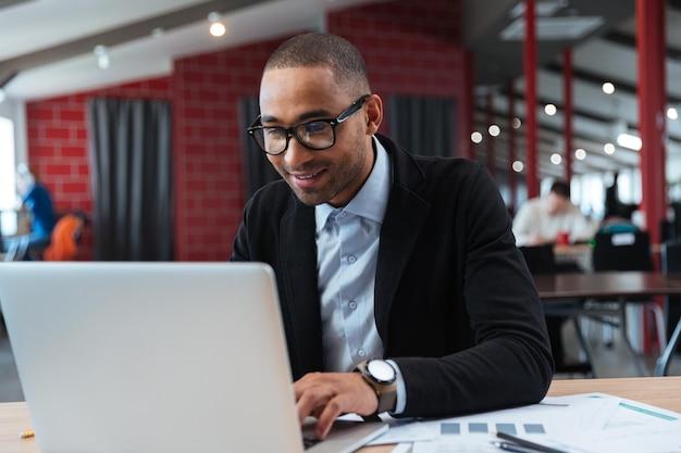 Молодой бизнесмен работает и набирает на ноутбуке в офисе