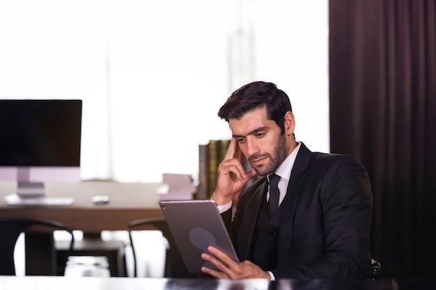 Молодой бизнесмен работает дома и о чем-то думает