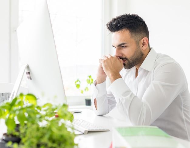 Молодой бизнесмен, работающих в офисе на компьютерном столе