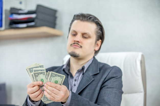 Young businessman working from his office and counting cash money