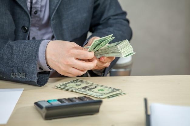 Giovane uomo d'affari che lavora dal suo ufficio e che conta denaro contante