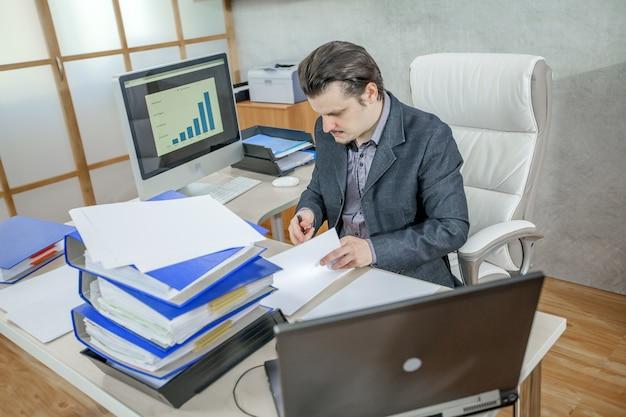 그의 사무실에서 일하는 젊은 사업가-열심히의 개념