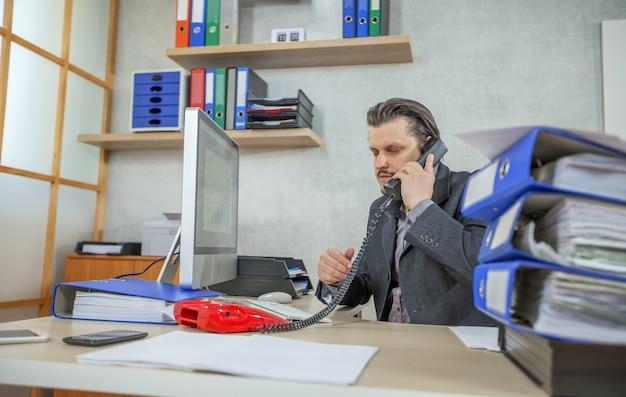 전화 통화하는 동안 그의 사무실에서 일하는 젊은 사업가