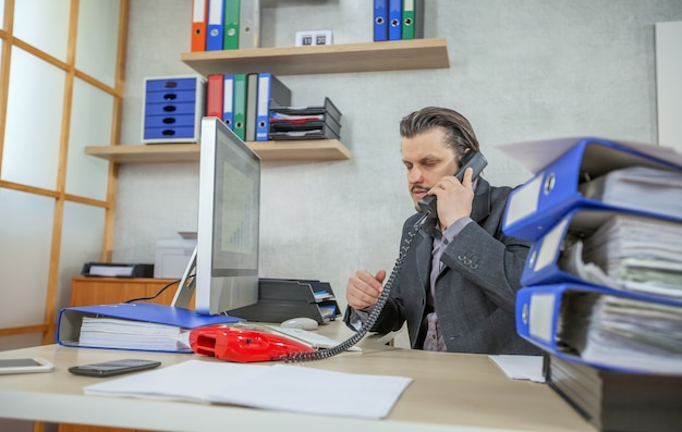 Young businessman working from his office while talking on the phone
