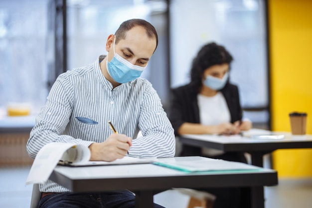 Young businessman working hard during pandemic of covid-19 at an office. male professional sitting at a desk wearing medical mask, checking business trends.