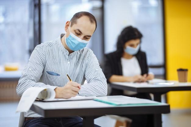 사무실에서 covid-19의 전염병 동안 열심히 일하는 젊은 사업가. 남성 전문 의료 마스크를 쓰고 책상에 앉아 사업 동향을 확인합니다.