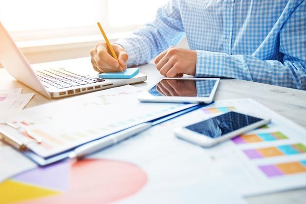 사무실에서 일하는 젊은 사업가. 나무 테이블, 논문, 문서, 통계에 노트북