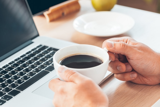Young businessman working at laptop computer with hot coffee in hand.