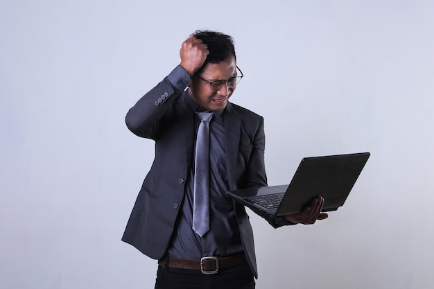 Young businessman working on laptop and looks frustrated