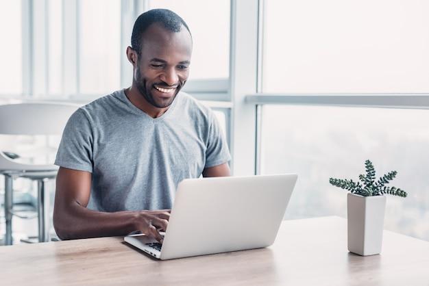 Молодой бизнесмен, работающий на своем ноутбуке в просторном светлом офисе