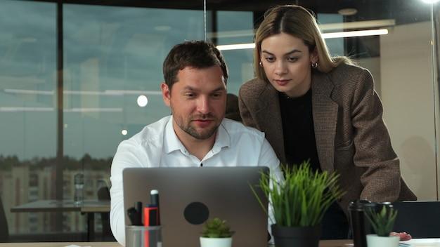 현대적인 개방형 사무실에서 책상에서 노트북 작업을 하는 젊은 사업가는 비공식 회의를 위해 여성 동료와 합류합니다.
