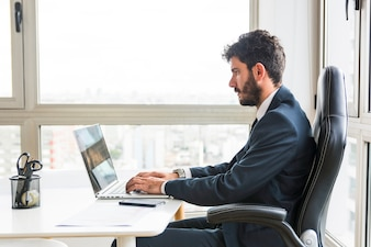 Young businessman working on laptop at workplace