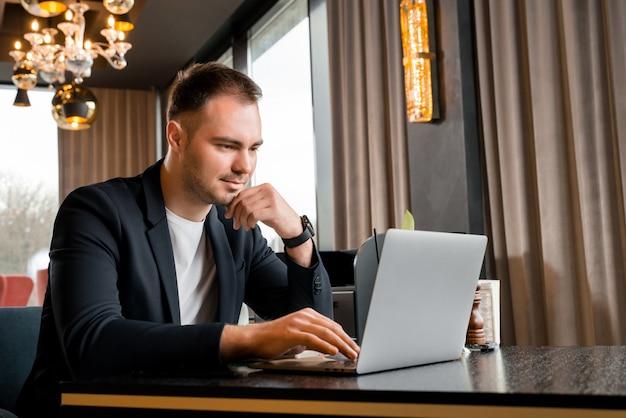 ホテルのモダンなカフェでラップトップに取り組んでいる青年実業家