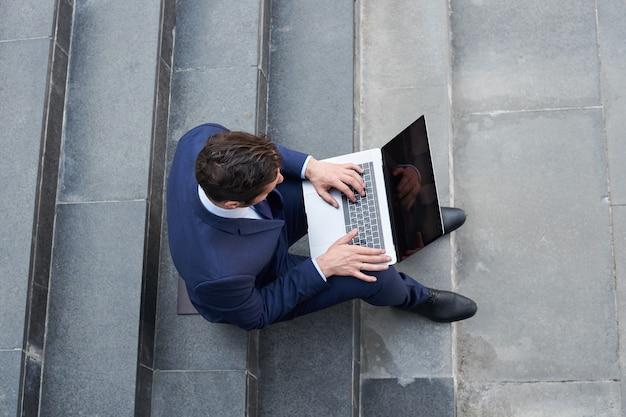 現代のラップトップに取り組んでいて、外の階段に座っている青年実業家、上面図
