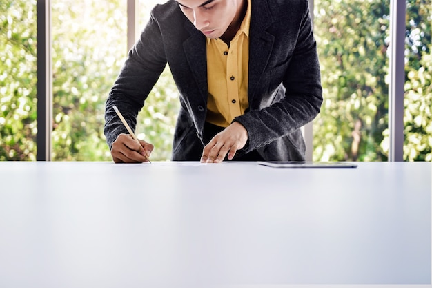 Young businessman working on the table in office by glass window