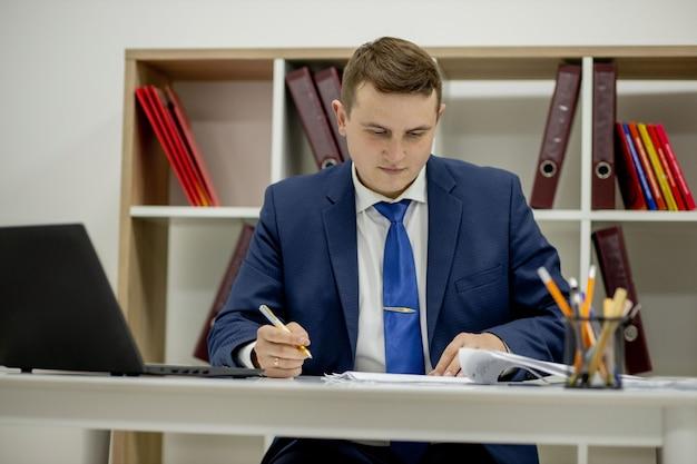 사무실 책상에 앉아 폴더에서 서류를 통해 찾고 문서 작업 젊은 사업가.