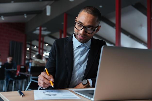 Молодой предприниматель, работающий с ноутбуком и написание заметок в офисе