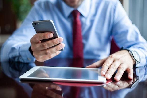 Молодой бизнесмен, работающий с современными устройствами, цифровым планшетным компьютером и мобильным телефоном. новые технологии для концепции рабочего процесса успеха.